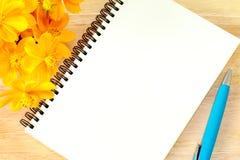 Κλείστε επάνω το ανοικτό κενό σπειροειδές βιβλίο σημειώσεων και το κίτρινο λουλούδι στο ξύλινο υπόβαθρο Στοκ Εικόνες