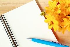 Κλείστε επάνω το ανοικτό κενό σπειροειδές βιβλίο σημειώσεων και το κίτρινο λουλούδι στο ξύλινο υπόβαθρο Στοκ φωτογραφία με δικαίωμα ελεύθερης χρήσης