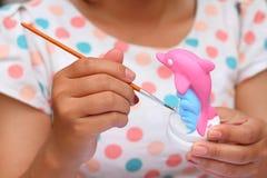 Κλείστε επάνω το ασβεστοκονίαμα δελφινιών watercolor χρωμάτων παιδιών τέχνης χεριών γυναικών Στοκ Εικόνα