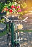 Κλείστε επάνω το εκλεκτής ποιότητας ποδήλατο με τα λουλούδια ανθοδεσμών στο καλάθι Στοκ Εικόνες
