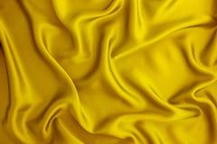 Κλείστε επάνω το κίτρινο χρυσό μετάξι κυμάτων ή το υπόβαθρο υφάσματος σατέν Στοκ Εικόνα
