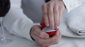 Κλείστε επάνω το κιβώτιο εκμετάλλευσης ατόμων με το δαχτυλίδι που κάνει να προτείνει στη φίλη του, εστιατόριο απόθεμα βίντεο