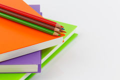 Κλείστε επάνω το μολύβι χρώματος και τη σπείρα σημειωματάριων - που δεσμεύονται στο άσπρο backgr Στοκ Εικόνες