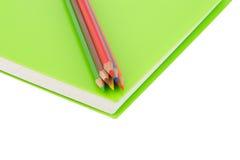 Κλείστε επάνω το μολύβι χρώματος και τη σπείρα σημειωματάριων - που δεσμεύονται στο άσπρο backgr Στοκ φωτογραφίες με δικαίωμα ελεύθερης χρήσης