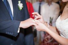 Κλείστε επάνω το νεόνυμφο βάζει το γαμήλιο δαχτυλίδι στη νύφη Στοκ Φωτογραφίες