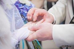 Κλείστε επάνω το νεόνυμφο βάζει το γαμήλιο δαχτυλίδι στη νύφη Στοκ Φωτογραφία