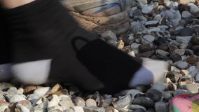 Κλείστε επάνω το ξύνοντας αμμοχάλικο Nosily ενηλίκων & παιδιών με τα παπούτσια από τις κάλτσες επάνω (ήχος) απόθεμα βίντεο
