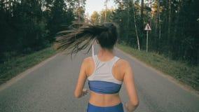 Κλείστε επάνω το παπούτσι και τα πόδια του jogger Πίσω πλάγια όψη ενός θηλυκού αθλητή που εκπαιδεύει έξω στο δρόμο στο πάρκο απόθεμα βίντεο