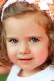 Κλείστε επάνω το πορτρέτο ενός γλυκού κοριτσιού ενός έτους βρεφών με τη ρόδινη επικεφαλής ζώνη και ένα τόξο, που φαίνεται ευθέος  στοκ εικόνες