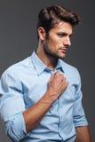Κλείστε επάνω το πορτρέτο ενός περιστασιακού ατόμου που κουμπώνει το πουκάμισό του Στοκ Εικόνα
