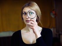 Κλείστε επάνω το πορτρέτο μιας όμορφης γυναίκας με ένα γυαλί πιό magnifier Στοκ Φωτογραφίες