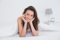 Κλείστε επάνω το πορτρέτο μιας όμορφης γυναίκας που στηρίζεται στο κρεβάτι Στοκ Εικόνα