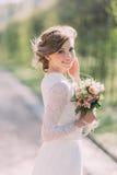 Κλείστε επάνω το πορτρέτο της μαγικής όμορφης νέας νύφης που φορά το κομψό άσπρο φόρεμα με την ανθοδέσμη στο πάρκο στοκ φωτογραφίες