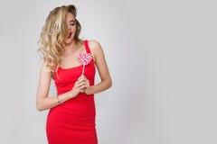 Κλείστε επάνω το πορτρέτο της νέας όμορφης γυναίκας με φωτεινό αποτελεί, κόκκινο φόρεμα και μεγάλο κόκκινο lollipop Στοκ φωτογραφία με δικαίωμα ελεύθερης χρήσης