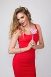 Κλείστε επάνω το πορτρέτο της νέας όμορφης γυναίκας με φωτεινό αποτελεί, κόκκινο φόρεμα και μεγάλο κόκκινο lollipop Στοκ Εικόνες