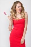 Κλείστε επάνω το πορτρέτο της νέας όμορφης γυναίκας με φωτεινό αποτελεί, κόκκινο φόρεμα και μεγάλο κόκκινο lollipop Στοκ εικόνα με δικαίωμα ελεύθερης χρήσης