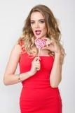 Κλείστε επάνω το πορτρέτο της νέας όμορφης γυναίκας με φωτεινό αποτελεί, κόκκινο φόρεμα και μεγάλο κόκκινο lollipop Στοκ εικόνες με δικαίωμα ελεύθερης χρήσης