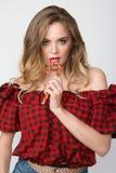 Κλείστε επάνω το πορτρέτο της νέας όμορφης γυναίκας με φωτεινό αποτελεί, κόκκινη κορυφή, σορτς τζιν και μεγάλο κόκκινο lollipop Στοκ Φωτογραφίες