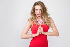 Κλείστε επάνω το πορτρέτο της νέας όμορφης γυναίκας με φωτεινό αποτελεί, κόκκινο φόρεμα και μεγάλο κόκκινο lollipop Στοκ Φωτογραφία