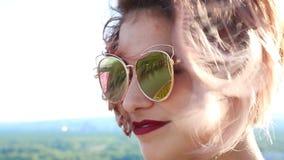 Κλείστε επάνω το πορτρέτο της όμορφης νέας γυναίκας στα γυαλιά ηλίου τρίχωμα μεταδιδόμενο μέσω του ανέμου απόθεμα βίντεο