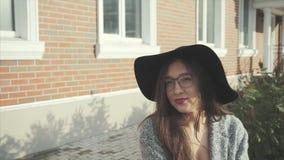Κλείστε επάνω το πορτρέτο της όμορφης χαμογελώντας γυναίκας στο μαύρο καπέλο και των γυαλιών υπαίθριων φιλμ μικρού μήκους