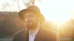 Κλείστε επάνω το πορτρέτο του γενειοφόρου νέου επιχειρηματία hipster που χαμογελά και που εξετάζει τη κάμερα στο ηλιοβασίλεμα στη απόθεμα βίντεο