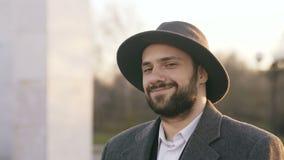 Κλείστε επάνω το πορτρέτο του γενειοφόρου νέου επιχειρηματία hipster που χαμογελά και που εξετάζει τη κάμερα στο ηλιοβασίλεμα στη φιλμ μικρού μήκους