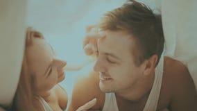 Κλείστε επάνω το πορτρέτο του ρομαντικών νεαρού άνδρα και της γυναίκας στο κρεβάτι στο σπίτι Σχέσεις, αγάπη, στενότητα απόθεμα βίντεο