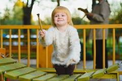 Κλείστε επάνω το πορτρέτο του χαριτωμένου xylophone παιχνιδιού κοριτσιών υπαίθριου στοκ φωτογραφίες