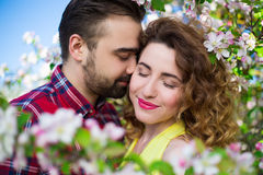 Κλείστε επάνω το πορτρέτο του όμορφου ζεύγους ερωτευμένο στον ανθίζοντας κήπο Στοκ Εικόνες