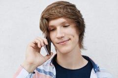 Κλείστε επάνω το πορτρέτο του όμορφου νέου αγοριού με τα στενά σκοτεινά μάτια, μοντέρνο hairdo, λακκάκι στο μάγουλο που κρατά το  στοκ φωτογραφίες με δικαίωμα ελεύθερης χρήσης