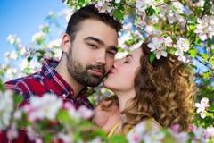 Κλείστε επάνω το πορτρέτο του όμορφου φιλήματος ζευγών στον ανθίζοντας κήπο Στοκ Φωτογραφία