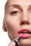 Κλείστε επάνω το πορτρέτο των ελκυστικών χειλιών της όμορφης γυναίκας Rouging τα χείλια της με το ρόδινο κραγιόν συντρόφων Η κυρί Στοκ Φωτογραφία