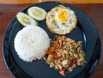 Κλείστε επάνω το ρύζι με ανακατώνει το τηγανισμένο κομματιασμένο χοιρινό κρέας, το τηγανισμένους αυγό και το βασιλικό Στοκ Εικόνα