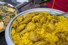 Κλείστε επάνω το ρύζι που μαγειρεύεται με το κοτόπουλο, τρόφιμα στην έκθεση σε αστικό Στοκ Εικόνα