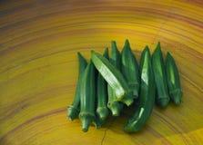 Κλείστε επάνω το φρέσκο πολλά από okra στο κίτρινο επιτραπέζιο υπόβαθρο Στοκ Εικόνες