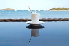 Κλείστε επάνω το φλυτζάνι καφέ στον ξύλινο πίνακα τροπική όψη παραλιών Στοκ εικόνες με δικαίωμα ελεύθερης χρήσης
