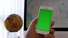 Κλείστε επάνω το χέρι που κρατά το πράσινο iphone οθόνης και που χρησιμοποιεί google το χάρτη απόθεμα βίντεο