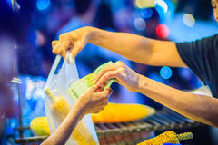 Κλείστε επάνω το χέρι του προμηθευτή τροφίμων οδών ψήνοντας και πωλώντας το φ στη σχάρα Στοκ Εικόνες