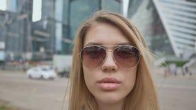Κλείστε επάνω το όμορφο πορτρέτο γυναικών μόδας και γοητείας φορώντας τα γυαλιά ηλίου Ένα κορίτσι με τα πολύβλαστα χείλια στο κλί φιλμ μικρού μήκους