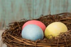 Κλείστε επάνω τριών ζωηρόχρωμων αυγών Πάσχας σε μια φωλιά Στοκ Εικόνες