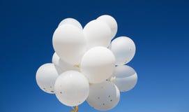 Κλείστε επάνω των άσπρων μπαλονιών ηλίου στο μπλε ουρανό Στοκ Φωτογραφίες