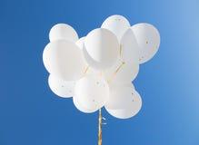 Κλείστε επάνω των άσπρων μπαλονιών ηλίου στο μπλε ουρανό Στοκ Φωτογραφία