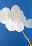 Κλείστε επάνω των άσπρων μπαλονιών ηλίου στο μπλε ουρανό Στοκ Εικόνες