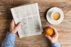 Κλείστε επάνω των αρσενικών χεριών με την εφημερίδα και τον καφέ Στοκ Φωτογραφία