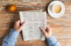 Κλείστε επάνω των αρσενικών χεριών με την εφημερίδα και τον καφέ Στοκ φωτογραφίες με δικαίωμα ελεύθερης χρήσης