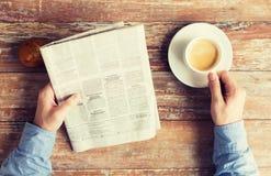 Κλείστε επάνω των αρσενικών χεριών με την εφημερίδα και τον καφέ Στοκ Εικόνα