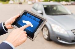 Κλείστε επάνω των αρσενικών χεριών με το εικονίδιο αυτοκινήτων στο PC ταμπλετών Στοκ Εικόνες