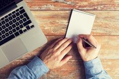 Κλείστε επάνω των αρσενικών χεριών με το lap-top και το σημειωματάριο Στοκ Εικόνα
