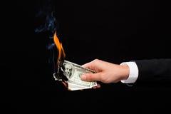 Κλείστε επάνω των αρσενικών χεριών χρημάτων δολαρίων εκμετάλλευσης καίγοντας Στοκ εικόνα με δικαίωμα ελεύθερης χρήσης